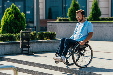 Handsome man in sunglasses using wheelchair on street looking at stairs without ramp