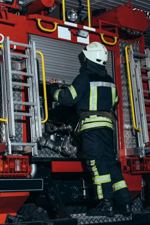Back view of firefighter in fireproof uniform and helmet closing truck at fire station Stock Photo