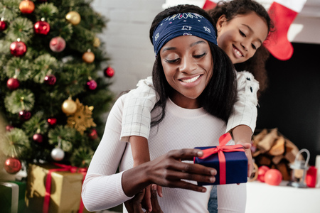 African American daughter hugging and gifting Christmas present to mother at home Stock Photo
