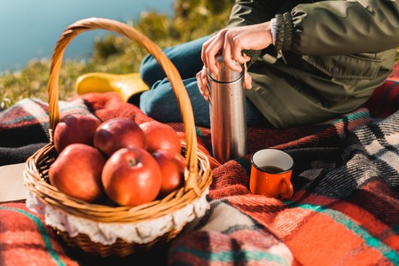 Cropped image of woman opening thermos while sitting on blanket with basket full of apples outdoors