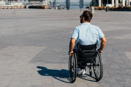 Back view of man in sunglasses using wheelchair on street