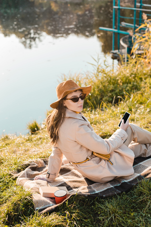 Beautiful stylish woman in hat and sunglasses holding smartphone and sitting on blanket near pond in park