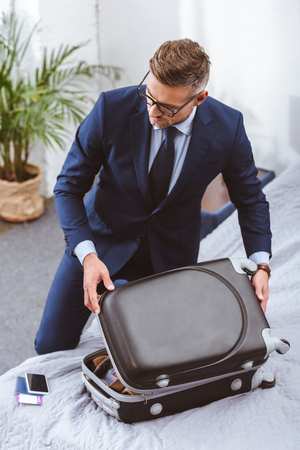 High angle view of businessman in suit and eyeglasses packing suitcase at home