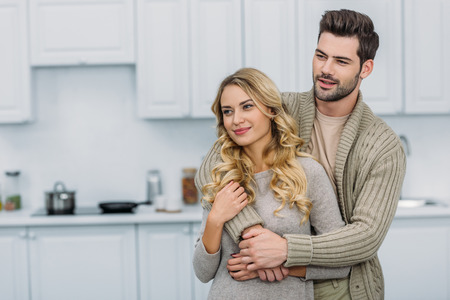 Handsome boyfriend hugging attractive girlfriend in kitchen and they looking away