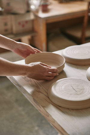 Cropped image of woman putting ceramic dish on table at workshop