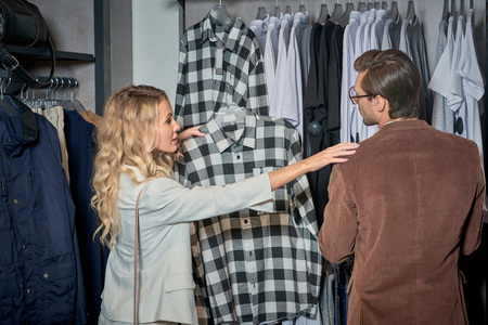 Young couple choosing stylish clothes together in boutique Foto de archivo - 111221548