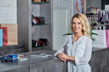 Beautiful young woman smiling at camera in shop Foto de archivo - 111221558