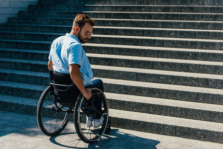 Handsome disabled man using wheelchair on street and stopping near stairs without ramp Archivio Fotografico - 111223645