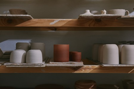 Ceramic bowls and dishes on wooden shelves at pottery studio Stok Fotoğraf