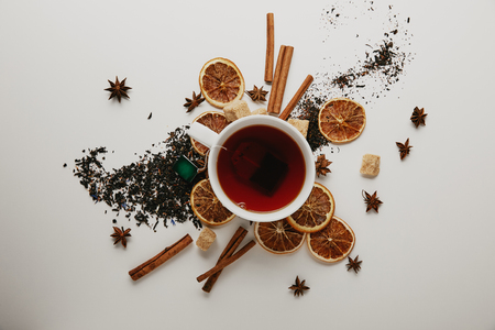 Flat lay with arranged cinnamon sticks, anise stars, dried orange pieces and cup of hot tea on white background