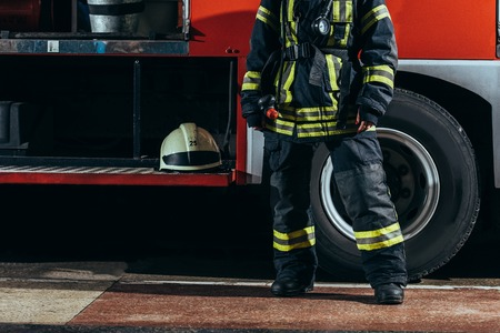 Partial view of female firefighter in protective uniform standing near truck with helmet at fire station