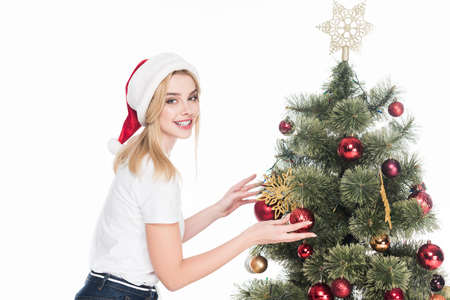 Side view of smiling woman in Santa Claus hat decorating Christmas tree isolated on white background