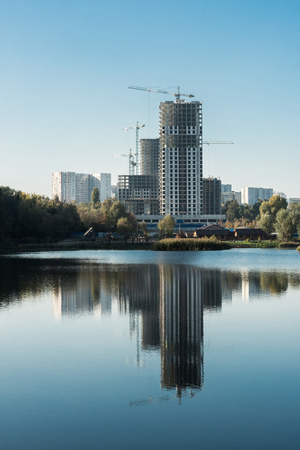Modern buildings with reflection in lake in city in autumn Фото со стока
