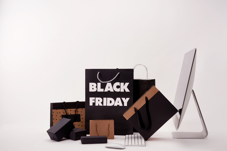 Side view of computer and various boxes with shopping bags with black Friday sign on white background Фото со стока - 111224719