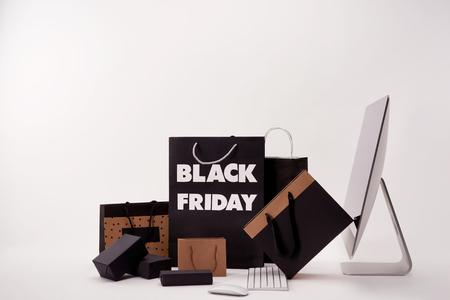 Vista laterale del computer e varie scatole con borse della spesa con segno del venerdì nero su sfondo bianco