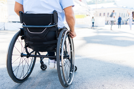 Cropped image of man using wheelchair on street Archivio Fotografico