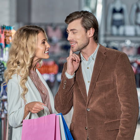 Attractive young woman with shopping bags able to kiss smiling man in store Foto de archivo - 111224735