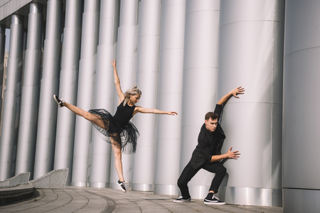 Beautiful young dancers in black clothes dancing near columns Imagens