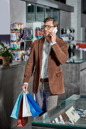 Handsome man in eyeglasses holding shopping bags and talking by smartphone in store Foto de archivo - 111224760