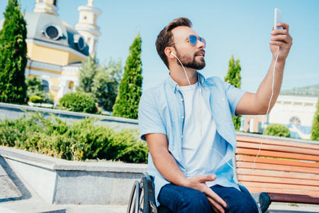 Handsome man in wheelchair taking selfie with smartphone and listening to music on street Stock Photo