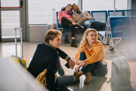 Young couple sitting on floor and looking away while waiting for flight in airport 写真素材