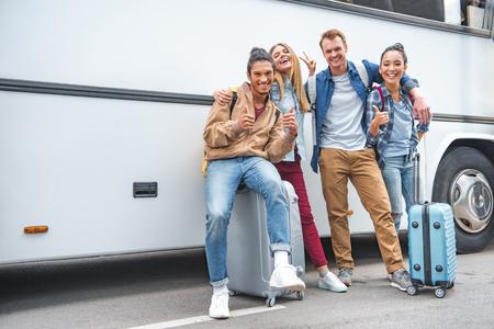 Glimlachende multi-etnische vrienden met tassen op wielen die duimen omhoog doen en vredesgebaren in de buurt van de reisbus