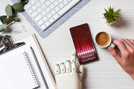Cropped image of businessman with prosthesis arm using smartphone with trading courses on screen at table with coffee cup in office Stock Photo
