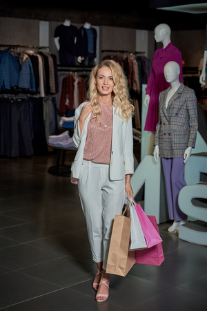 Beautiful young woman holding shopping bags and smiling at camera in fashion store Foto de archivo - 111225103