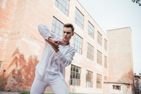 Low angle view of handsome young man in white clothes dancing on street Foto de archivo - 111225109