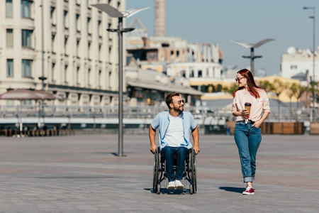 Handsome boyfriend in wheelchair and girlfriend with having walk in city and looking at each other Stock Photo