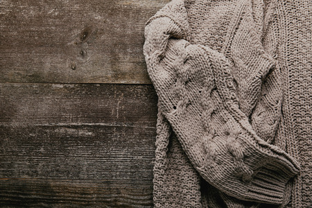 Top view of grey knitted sweater on wooden tabletop
