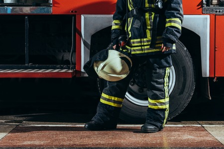 Partial view of female firefighter in protective uniform with helmet in hand standing near truck at fire station Foto de archivo