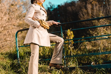 Partial view of elegant stylish woman in trench coat posing outdoors