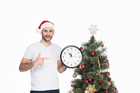 Portrait of man in Santa Claus hat pointing at clock while standing near Christmas tree isolated on white background