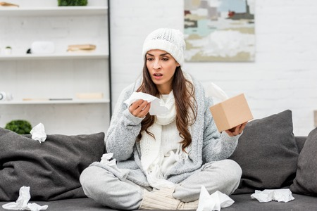 Sick young woman in warm clothes sitting on messy couch and sneezing with paper napkins at home