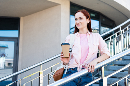 Attractive redhair woman in pink shirt looking away, leaning on railing and holding disposable coffee cup
