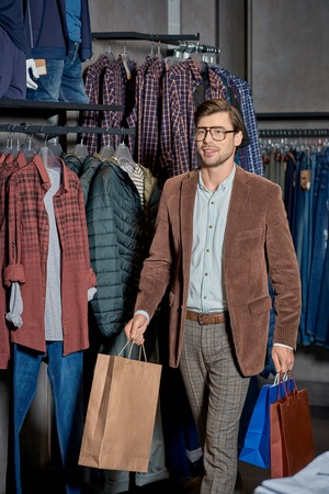 Handsome smiling man holding shopping bags and looking away in store Foto de archivo - 111272536