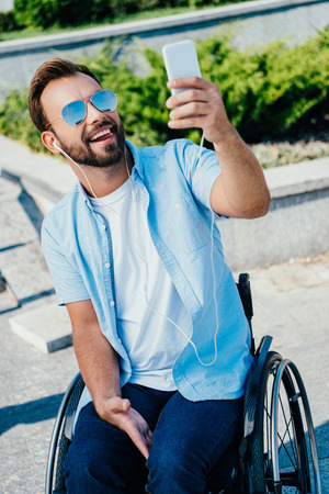 Handsome man in wheelchair sticking tongue out and taking selfie with smartphone on street