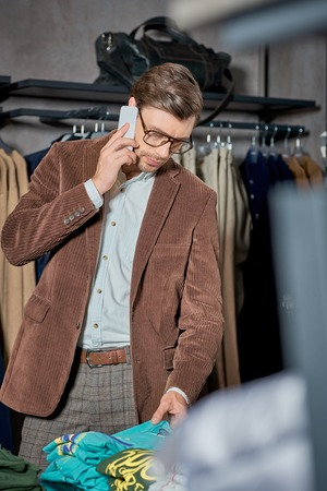 Handsome man talking by smartphone and looking at stylish clothes in shop Foto de archivo - 111225343