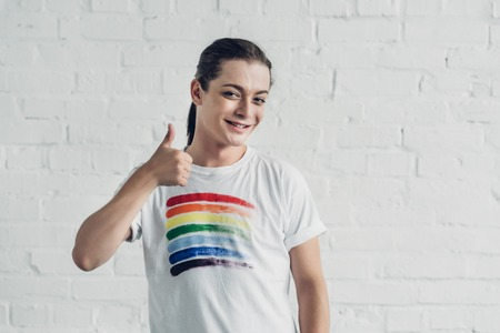 Happy transgender man in white t-shirt with pride flag showing thumb up in front of white brick wall background Stockfoto