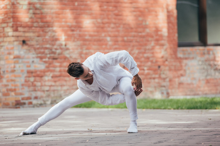 Handsome young male dancer in white clothes dancing on urban street