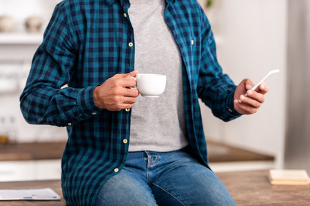 Cropped shot of man in checkered shirt holding cup of coffee and using smartphone at home 版權商用圖片