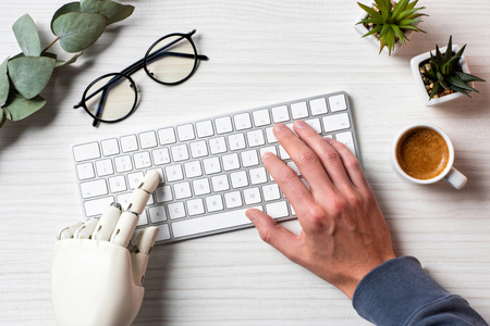 Cropped image of business with prosthesis hand typing on computer keyboard at table in office Stock Photo