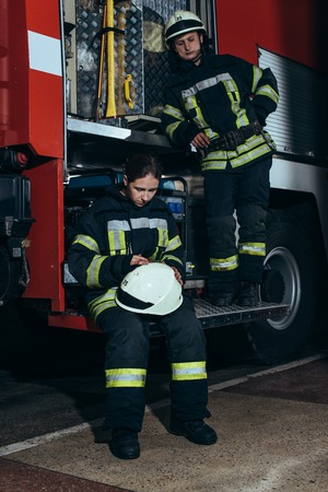 Firefighters in protective uniform near truck at fire department Stockfoto