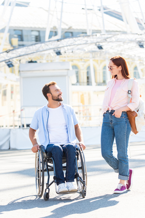 Smiling handsome boyfriend in wheelchair and girlfriend looking at each other on street