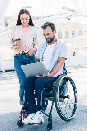 Handsome boyfriend in wheelchair using laptop and girlfriend standing with coffee to go on street Stock Photo