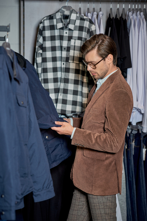 Handsome man in eyeglasses looking at jacket while shopping in boutique Foto de archivo - 111344829