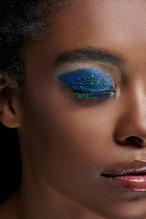 Partial view of African American woman with bright blue eye shadow isolated on blue background