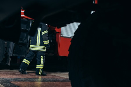 Partial view of firefighter in protective fireproof uniform walking at fire station Stock Photo