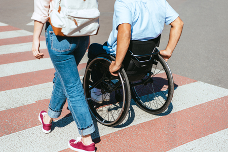 Cropped image of disabled boyfriend in wheelchair and girlfriend crossing crosswalk in city